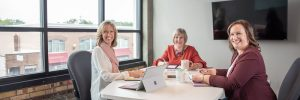 Three women sitting at conference table working