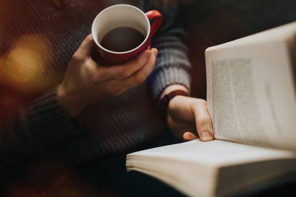 Person reading book and holding mug of coffee
