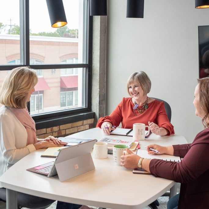 women smiling while working together at table